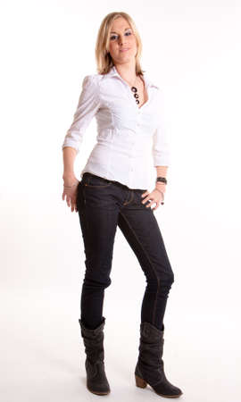 Young blond woman in jeans and boots standing against a white background Stock Photo - 9522477