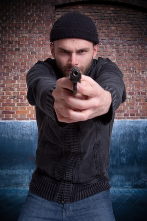 malefactor:   Dangerous looking man holding a gun aiming at you in an urban background