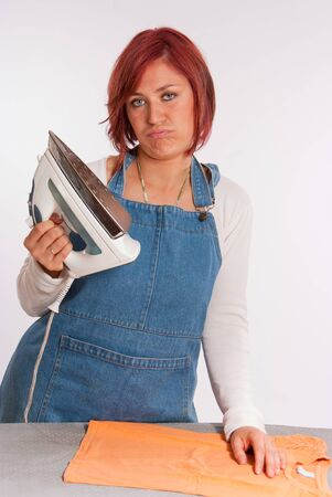 Woman looking with disgust at her iron   Stock Photo - 9548404