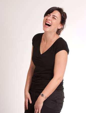 hilarity:  Portrait of a laughing attractive green eyed  brunette  dressed in black  Stock Photo
