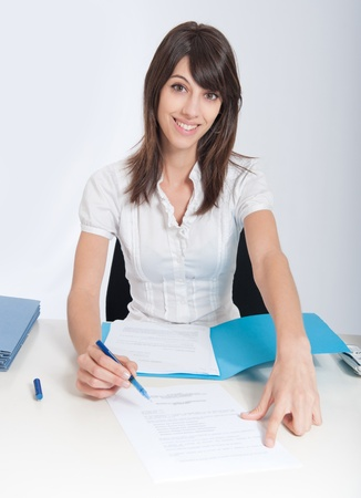 Smiling young woman at a desk pointing a document section with her pen Stock Photo - 9548741