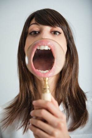 Young woman showing her mouth thru a magnifying glass Stock Photo - 9548400