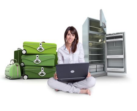 Young woman using a laptop with a pile of suitcases and an empty fridge on the background   Stock Photo - 9548876