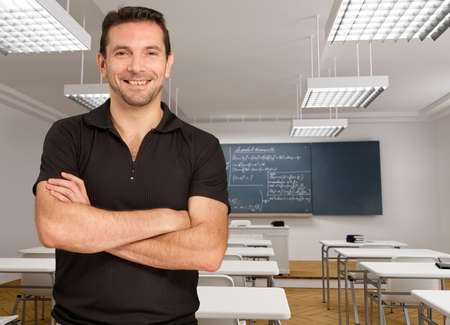 adults learning:   Portrait of a smiling teacher in an empty classroom