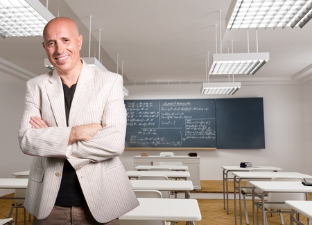 formulae:   Portrait of a smiling mature teacher in an empty classroom