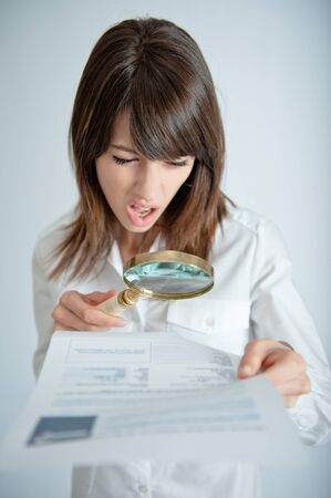 legal document:   Young woman reading a document through a magnifying glass with a shocked expression