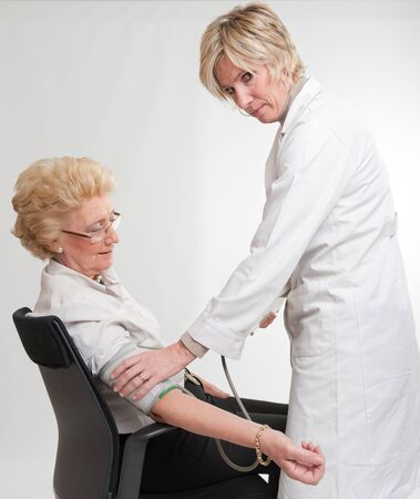 Doctor checking a lady's blood pressure Stock Photo - 9602944