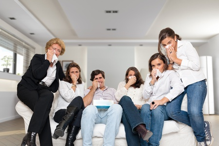 handkerchief:   A group of family members sitting at home crying watching tv