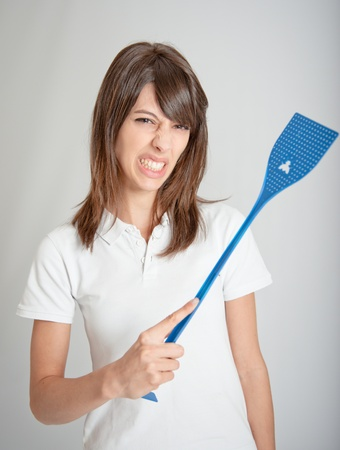 Annoyed girl holding a flyswatter Stock Photo - 9602973