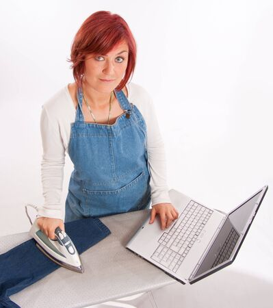 Woman with apron ironing and using her computer simultaneously  photo
