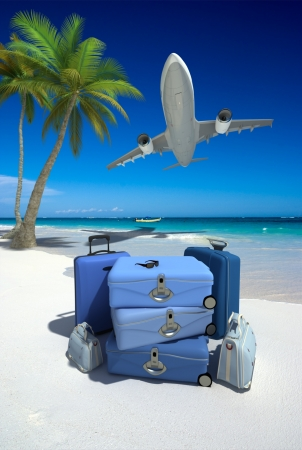 Pile of blue luggage on a tropical beach and a flying plane