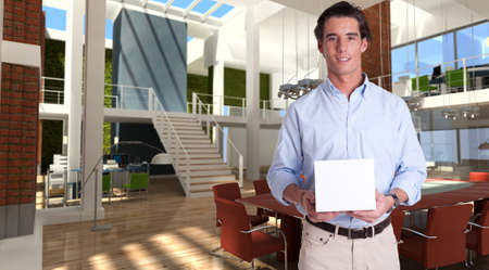 Cheerful young man holding a white box in a modern luxurious office   photo