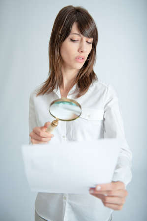 Young woman inspecting closely a document through a magnifying glass   photo