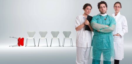 malpractice:  Serious medical staff with a row of white chairs an a fallen red one on the background
