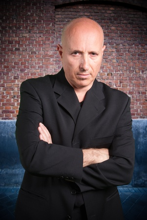 Tough looking mature man in a black suit on an urban background  Stock Photo - 9676674