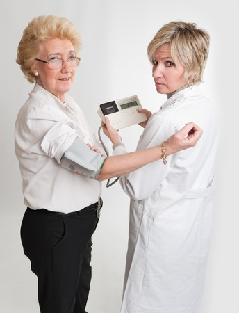 Doctor checking a lady's blood pressure Stock Photo - 9800457