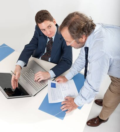 Two businessmen looking at a laptop photo