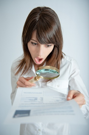 Young woman reading a document through a magnifying glass with a shocked expression     photo