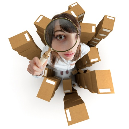 locate:   Young woman with a magnifying glass and piles of cardboard boxes   Stock Photo