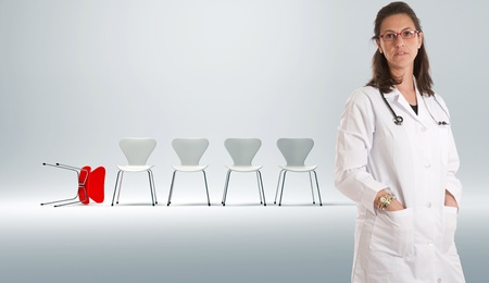 malpractice:   Serious female doctor with a row of white chairs on the background and a red fallen one