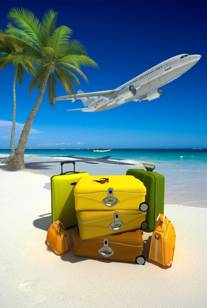 Pile of yellow luggage on a tropical beach and a flying plane  Stock Photo
