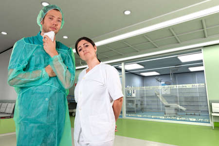 Surgeon in operating cloths and nurse in a clinic interior  photo