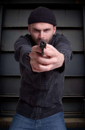 goon:  Dangerous looking man holding a gun aiming at you in an urban background