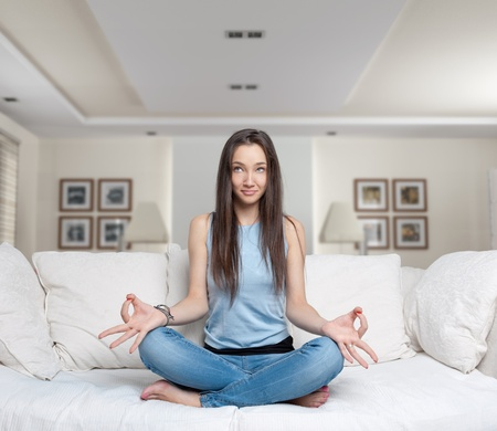 Young woman sitting on a sofa in the lotus position meditating Stock Photo - 9800451