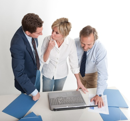 Three business people looking at a laptop computer  photo