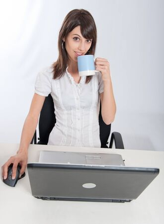 Young woman sitting at her desk holding a coffee mug    photo