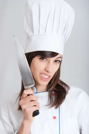 menacing:   Young female chef holding a knife with a menacing expression   Stock Photo