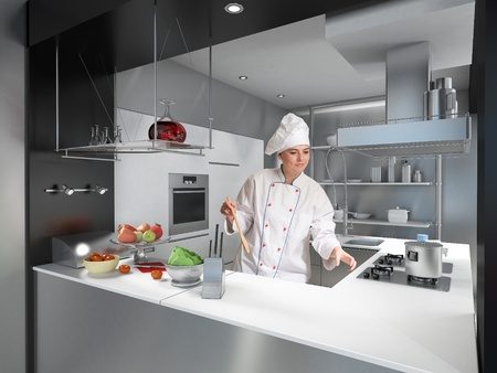 stainless steel kitchen:  Young woman with cooks uniform and toque in a modern industrial kitchen  Stock Photo