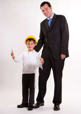 Cute cheerful boy with thumbs up wearing a safety helmet and holding a plan with his dad  photo