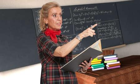 towards:  Maths teacher pointing towards the class with a blackboard as background