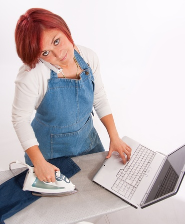 Woman with apron on the phone, while ironing and using a computer   photo