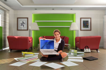 Schoolgirl holding a computer in the middle of a chaotic living room full of documents and files Stock Photo - 9948112