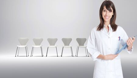 Nurse with a row of white chairs at the background   photo