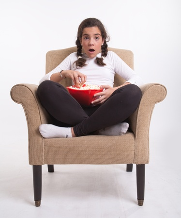 captivation:  Girl sitting on an armchair with a popcorn bowl looking open-mouthed