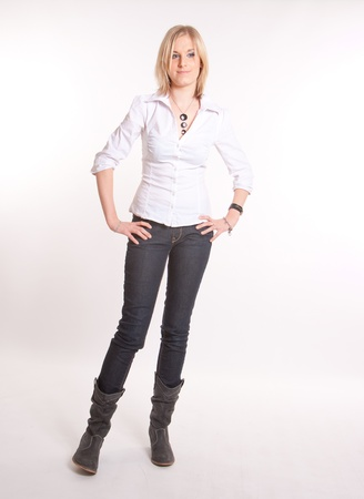 jeans boots:  Young blond woman in jeans and boots standing against a white background