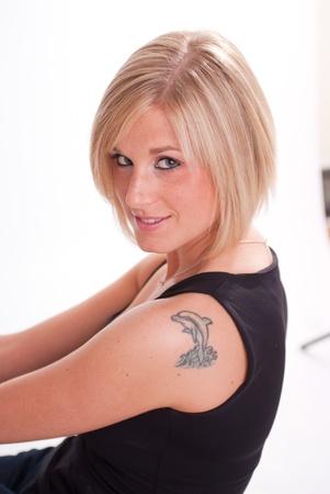 delfin: Atrakcyjna blondynka z delfinem tatuaż na ramieniu Zdjęcie Seryjne
