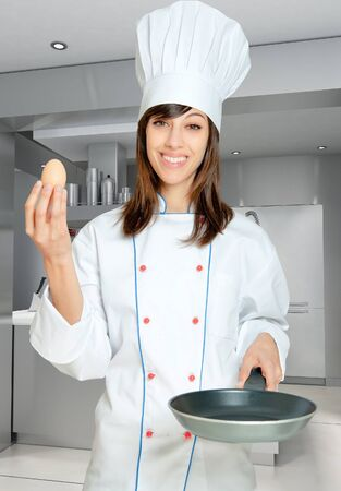 countertop:  Young woman in chef�s  attire with an egg and a frying pan