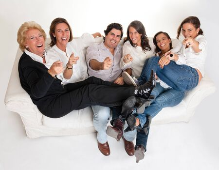 Family group sitting on a sofa laughing and pointing to the camera   Stock Photo - 10072884