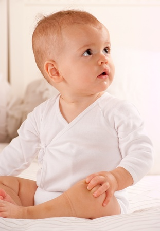 Cute baby sitting on a bed dressed in a bodysuit  photo