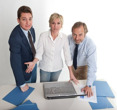 Three people around a laptop looking at the camera  photo