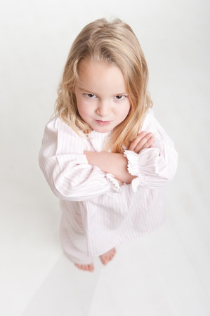 tantrum:  Aerial view of a cute little blonde girl with an angry expression in her pajamas  Stock Photo