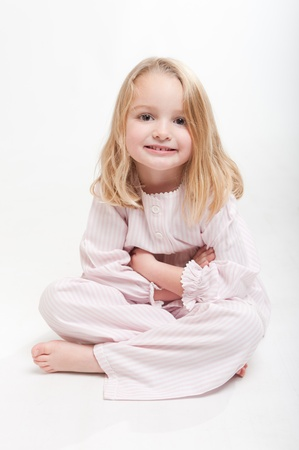 nighttimes:  Cute little blonde girl in her pajamas sitting on the floor  Stock Photo