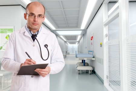 corridors:   Doctor taking notes at the entrance of  a hospital corridor