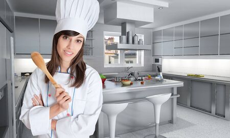 countertop:    Young female chef holding a wooden spoon   Stock Photo