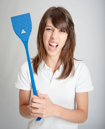 kill:   Annoyed girl holding a flyswatter   Stock Photo