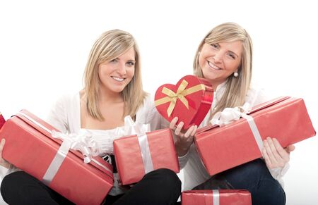 Two young sisters surrounded by gift boxes, some of them heart shaped Stock Photo - 10441905